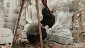 8 de marzo de 2016 Mandalay, Myanmar La secuencia video - sirva la talla en el mármol y la mujer que acaban la estatua de Buda en almacen de metraje de vídeo