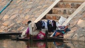 5 de marzo de 2016 Nyaungshwe, Myanmar Mujeres que lavan la ropa en el banco del río en Myanmar - secuencia de 2 vídeos almacen de metraje de vídeo