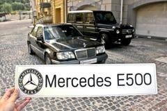 31 de marzo de 2015, Kiev El individuo que lleva a cabo la muestra 'Mercedes E500 'en el fondo de Mercedes imagen de archivo libre de regalías
