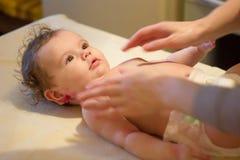 De massage van de baby Massagist die tot massage maken aan een kleine baby stock afbeelding