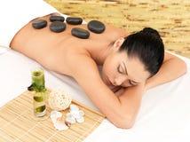 De massage van de steen voor vrouw bij kuuroordsalon. stock afbeeldingen