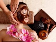 De massage van het kuuroord voor vrouw met gezichtsmasker op gezicht stock fotografie