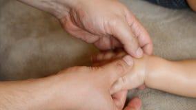 De massagetherapeut doet voor de van het de jongenskind van de één éénjarigebaby de rehabilitatiemassage stock videobeelden