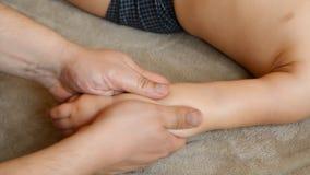 De massagetherapeut doet voor de van het de jongenskind van de één éénjarigebaby de rehabilitatiemassage stock video