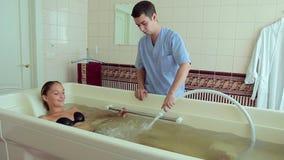 De masseur maakt een vrouw tot een massage bij hydrobath stock footage