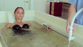 De masseur maakt een vrouw tot een massage bij hydrobath stock videobeelden