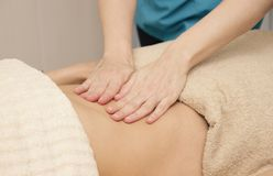 De masseur maakt helende massage van de buik voor een vrouw stock foto