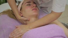 De masseur maakt massage van hals en decollete van vrouw in kliniek stock video