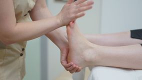 De masseur maakt tot een therapeutische voetmassage aan het meisje Close-up stock video