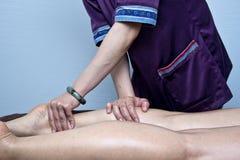 De masseuse doet massage op het been voor vrouwelijke klant Royalty-vrije Stock Fotografie