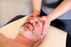 De masseuse van mensenhanden voor massage het hoofd van een kerel Royalty-vrije Stock Foto