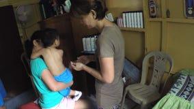 De masseusehand masseert de baby` s rug stock footage