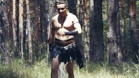 De massieve barbaarse mens met naakt torso houdt een bijl in het bos stock video
