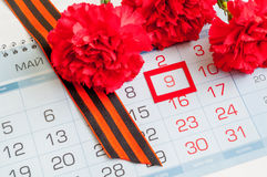 9 de mayo - clavel rojo con la cinta de George que miente en el calendario con la fecha del 9 de mayo Foto de archivo