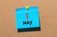 1 de mayo día 1 del mes, calendario en el tablón de anuncios del corcho, fondo del negocio Tiempo de primavera, espacio vacío par Imagenes de archivo