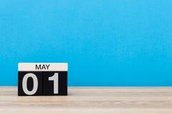 1 de mayo día 1 del mes, calendario en fondo azul Día de primavera, espacio vacío para el texto Día internacional del ` de los tr Imágenes de archivo libres de regalías