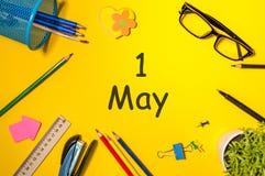 1 de mayo día 1 del mes, calendario en la tabla de la oficina de negocios, lugar de trabajo en el fondo amarillo Tiempo de primav Fotografía de archivo libre de regalías