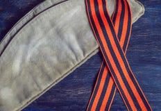 9 de mayo día de la victoria, casquillo militar y cinta de San Jorge en un fondo azul Foto de archivo libre de regalías