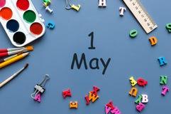 1 de mayo el día 1 de puede el mes, calendario en la tabla de la escuela, lugar de trabajo en el fondo azul Tiempo de primavera,  Fotos de archivo libres de regalías