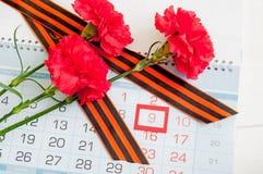 9 de mayo el fondo con tres claveles rojos y la cinta de San Jorge en el calendario con el 9 de mayo fechan Imagen de archivo