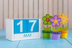 17 de mayo La imagen de puede calendario de madera del color 17 en el fondo blanco con las flores Día de primavera, espacio vacío Imagen de archivo