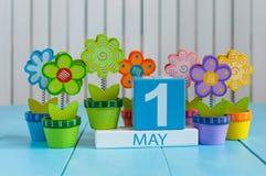 1 de mayo la imagen de puede 1 calendario de madera del color en el fondo blanco con las flores Día de primavera, espacio vacío p Imagen de archivo libre de regalías