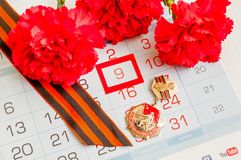 9 de mayo tarjeta festiva con la medalla del jubileo de la gran guerra patriótica, de claveles rojos y de la cinta de San Jorge Imágenes de archivo libres de regalías