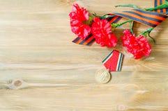 9 de mayo tarjeta - medalla del jubileo de la gran guerra patriótica con los claveles y la cinta rojos de San Jorge Fotografía de archivo libre de regalías