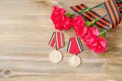 9 de mayo tarjeta - medallas del jubileo de la gran guerra patriótica con los claveles y la cinta rojos de George Foto de archivo libre de regalías