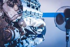 De mechanische handen halen noot met moersleutel aan terwijl het herstellen van motor Royalty-vrije Stock Foto's