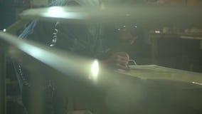 De mechanische volwassen mens in een zwart jasje en een GLB trekt met een borstel op autokap in garage stock footage