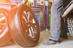 De mechanische wielen van arbeidersveranderingen op auto in garage van de autoreparatiedienst winkelen Stock Fotografie
