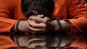De medebewoner houdt zijn hoofd in wanhopig, voelt spijt over het begaan van misdaad, close-up stock fotografie