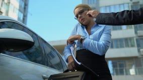 De medewerker geeft autosleutels aan bezige vrouw, krijgt de dame in auto, haast zich aan vergadering stock footage