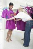 De medewerker helpt Vrouw Fuschia Raincoat overwegen Stock Fotografie