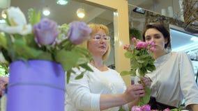 De medewerker leert om bloemboeket onder supervisie van bloemist te creëren stock video