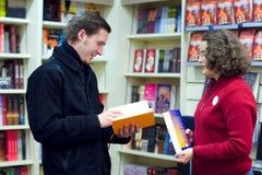 De medewerker van de boekhandel en de klant stock foto's