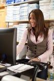 De medewerker van de winkel bij contant geld Stock Afbeeldingen