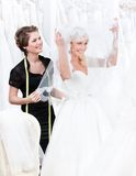 De medewerker van de winkel helpt aan de bruid om weddi te zetten Stock Afbeeldingen