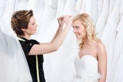 De medewerker van de winkel helpt om de huwelijkstiara te bevestigen Stock Afbeelding