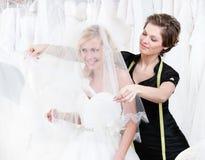 De medewerker van de winkel plaatst de sluier van de bruid Royalty-vrije Stock Afbeelding