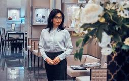 De medewerker van de elegante juwelenboutique wacht op klanten in haar elegante winkel royalty-vrije stock foto