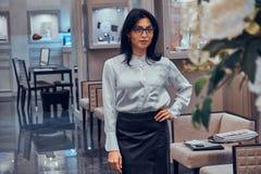 De medewerker van de elegante juwelenboutique wacht op klanten in haar elegante winkel stock fotografie