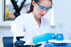 De medewerker van het meisjeslaboratorium controleert steekproeven medisch laboratorium Royalty-vrije Stock Fotografie
