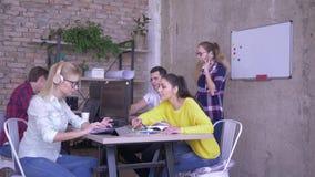De medewerkers in bureau werken bij lijst in hoofdtelefoons met laptops en computers aan achtergrond van bedrijfswerknemer met stock footage