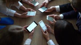 De medewerkers kijken in hun smartphones samen op werkplaats stock footage