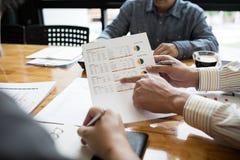 De medewerkers zijn adviseurs op bedrijfsdocumenten, belasting stock foto