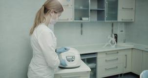 De medische hulp neemt het bloed van een donor en het zetten van op het medische machinelaboratorium aan analyse het bloed stock video