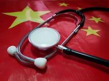 De medische stethoscoop is bereid om griep te verhinderen die over de hele wereld uitspreidt De achtergrond is de vlag van China stock afbeeldingen