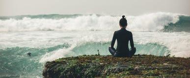 De meditatie van de yogavrouw bij de rand van de kustklip stock foto's